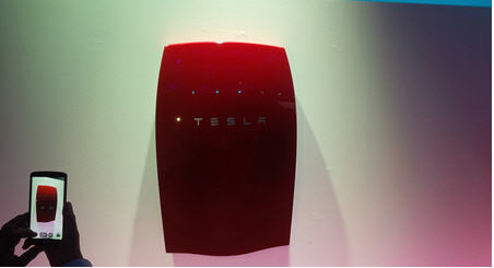 Tesla's evolves with low cost utility batery launch - battery on wall