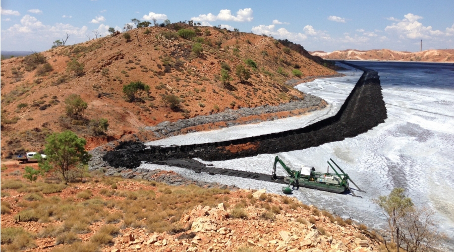 Watermaster creating a new channel to level water in a tailings dam
